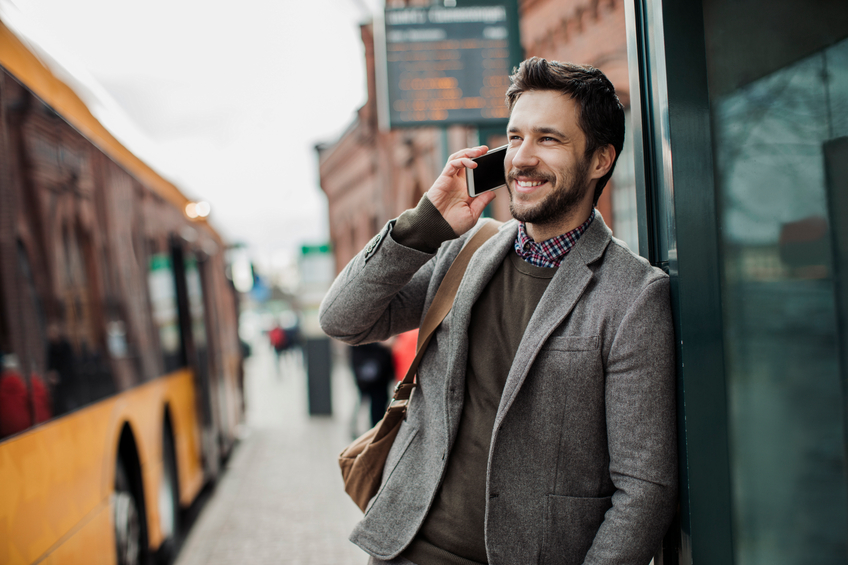 Photo of a businessman on the  phone at bus station